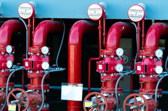 Main supply water piping in the fire extinguishing system. Fire sprinkler system with red pipes. Fire suppression. Manual valve of Fire extinguisher system.