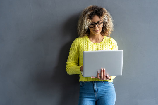 Young happy smiling woman in casual clothes holding laptop and sending email to her best friend.