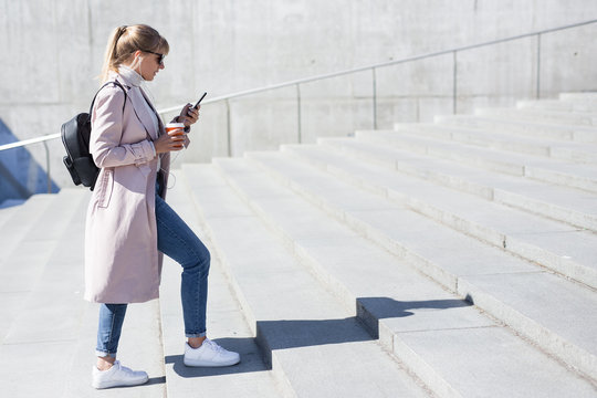 success and career concept - side view of young woman walking up the stairs