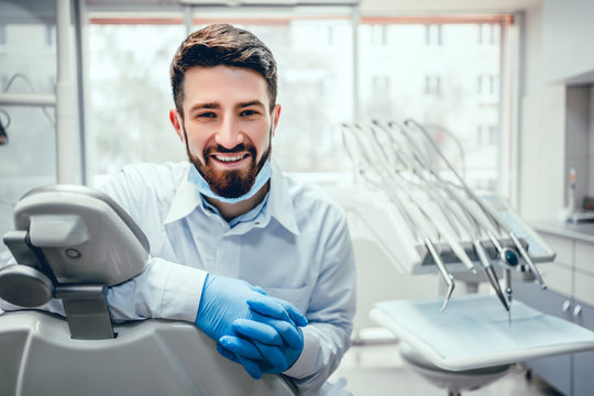 Front view of professional male dentist in white doctor coat and protective gloves sitting in dental chair and equipment, looking at camera and smiling. Bearded man posing during working process.