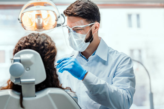 Dentist working in dental clinic with patient in the chair.