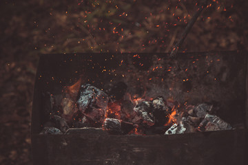 charcoal smolder in the iron grill. cooking picnic outdoors. sparks over the embers top view close up