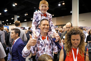 Ray Renk holds his 10-year-old son Benjamin as they wear matching custom-made suits printed with a caricature of Berkshire Hathaway Chief Executive Warren Buffett at the annual shareholder meeting in Omaha
