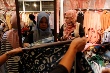 Women shop for hijabs at a stall at MUFFEST in Jakarta
