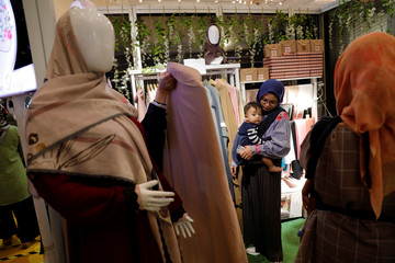 Woman carries a boy as she shops for hijabs at MUFFEST in Jakarta