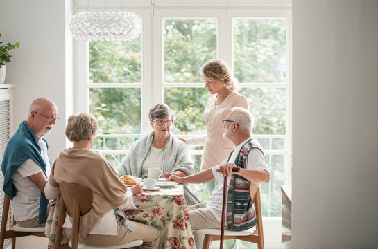 Group of senior friends with helpful carer sitting together at the table at nursing home dining room
