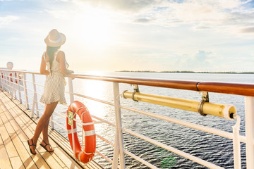 Wall Mural - Luxury cruise ship travel elegant tourist woman watching sunset on balcony deck of Europe mediterranean cruising destination. Summer vacation cruiseship sailing away on holiday.
