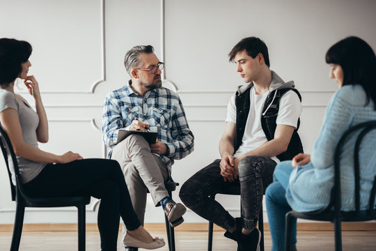 Group therapy session with psychologist and depressed man and woman