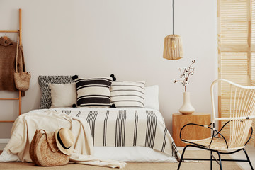 Striped bedding on comfortable king size bed in contemporary bedroom interior with wicker chair and copy space on empty wall