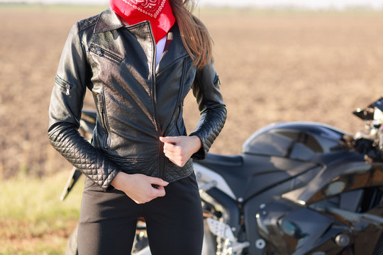 Faceless woman biker dressed in black clothes and red bandana on neck, keeps hand on her jacket, poses on road near her modern fast bike, stops her motobike and having rest. Outdoor lifestyle concept.