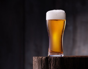 Glass of light beer on wooden table with wooden background