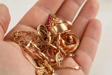 Pile of gold jewellery in hand, closeup shot Wall mural