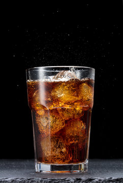 glass of cola with ice on black background