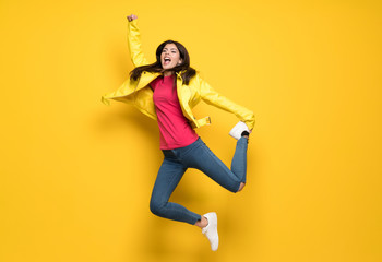 Teenager girl jumping over isolated yellow wall Fototapete