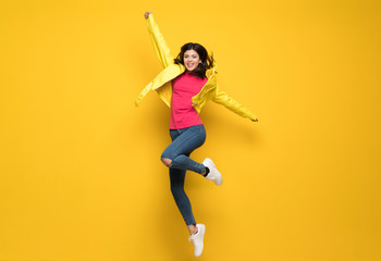 Teenager girl jumping over isolated yellow wall Wall mural