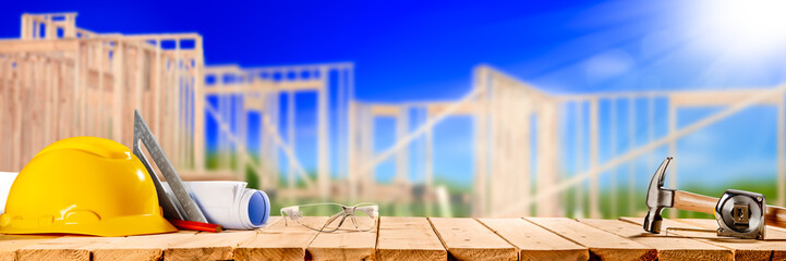 Construction Tools On Wooden Table With New House Framework In Background - Housing Industry Concept