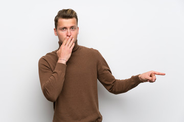 Blonde man over isolated white wall pointing finger to the side with a surprised face