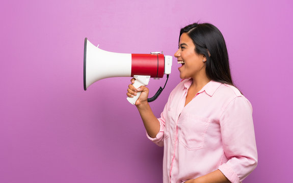 Young Colombian girl over purple wall shouting through a megaphone