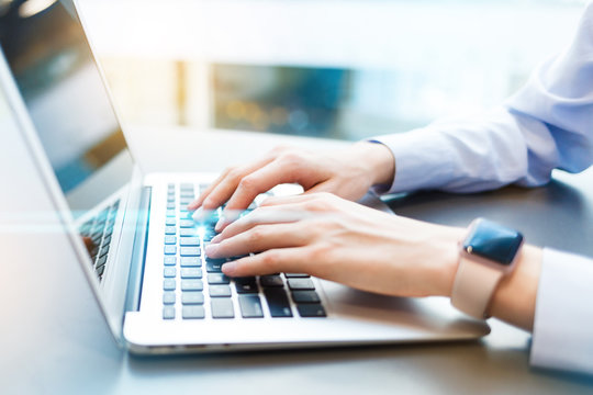 Business woman working in modern sunny office on modern laptop. Closeup of female hands typing on notebook keyboard. Toned. Light blurred background. Concept of new technology