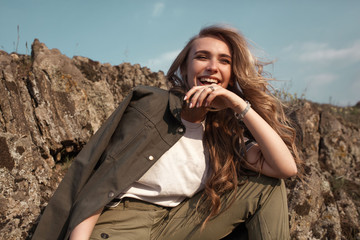 High fashion portrait of stylish beautiful woman in trendy jackets and jeans posing outdoor. Vogue style.
