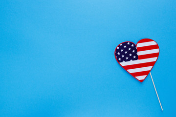 Photo booth for 4th of July. Heart on sticks on blue background. American flag colors. Independence Day, patriotic holiday background