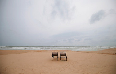 Empty sunbathing chairs are seen on a beach near hotels in a tourist area in Bentota