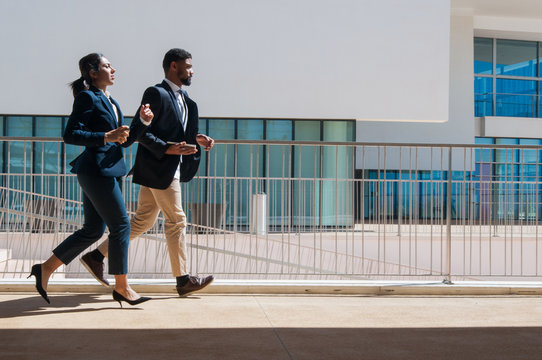 Business man and woman running outdoors. Business people wearing formal clothes with building in background. Business competition concept. Side view.