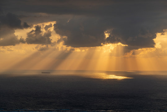 Sun Rays pouring through the clouds into the sea and a container ship