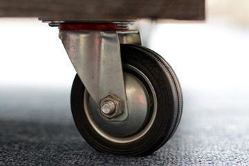 Caster wheel placed under a drawer unit, close-up