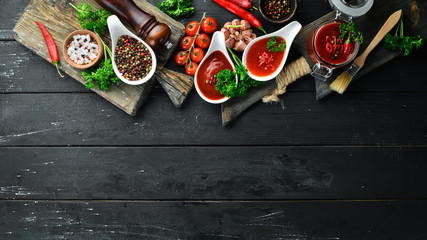 Set of red sauces on a wooden background. Ketchup, barbecue sauce, tomato sauce. Top view. Free space for your text. Wall mural