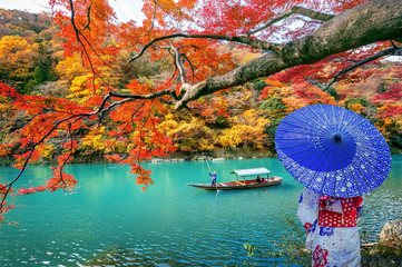 Wall Mural - Asian woman wearing japanese traditional kimono at Arashiyama in autumn season along the river in Kyoto, Japan.