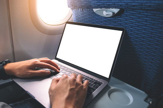 Mockup image of a man using and typing at laptop computer with blank white desktop screen while sitting in the cabin