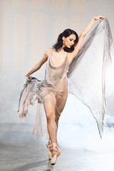 Beautiful dark-haired Arabian female dancer dancing in grey transparent costume with cape on head in white studio
