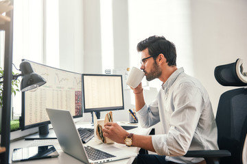 Coffee break. Young bearded businessman or trader is drinking a coffee and eating a sandwich while looking at monitor screen with financial data in his modern office