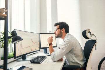 Busy working. Handsome bearded trader in formal wear and eyeglasses is analyzing trading charts and financial data on computer screens while sitting in his modern office. Wall mural