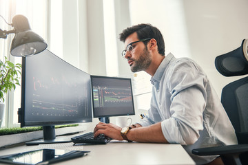 Confident businessman. Young bearded trader in formal wear is analyzing trading charts on computer screens while sitting in his modern office