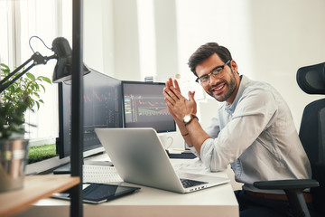 Young and successful. Happy bearded trader in formal wear and eyeglasses looking at camera and...