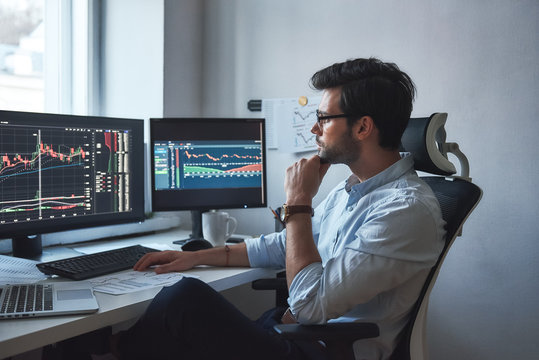 Busy working day. Side view of successful trader or businessman in formal wear and eyeglasses working with charts and market reports on computer screens in his modern office
