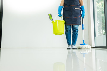 Young housekeeper cleaning floor mobbing holding mop and plastic bucket with brushes, gloves and detergents in the leaving room house floor helping his wife.