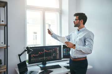 Trading strategy. Smart and young trader in eyeglasses looking at financial reports and analyzing trading charts while standing in front of computer screens in modern office.