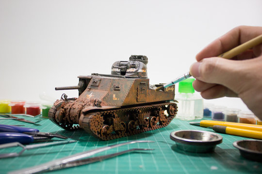 Painting plastic model WW2 tank M3 Lee with part and tools on wooden workbench closeup.