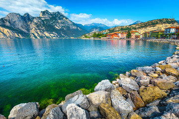 Wall Mural - Lake shore with rocks and mountains in background, lake Garda