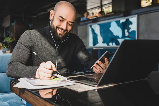 Businessman is working on laptop, making notes in document, speaks in headphones on cell phone while sitting at table in cafe.