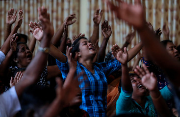 Members of Zion Church, which was bombed on Easter Sunday, pray at a community hall in Batticaloa