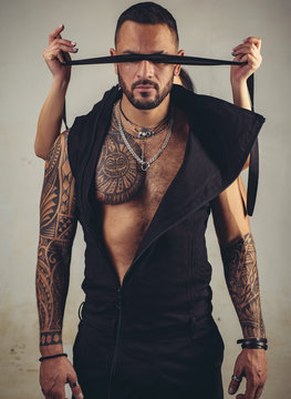 trust concept. muscular macho man with athletic body. brutal sportsman. steroids. dominating. sexy abs of tattoo man. male fashion. female hands cover his eyes with rope. censorship. Human Right day