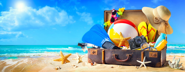 Beach accessories in suitcase on sand. Family holidays concept Wall mural