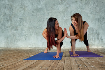 Two smiling beautiful, fitness girls doing exercises in the fitness room give five. Concept sport, teamwork.