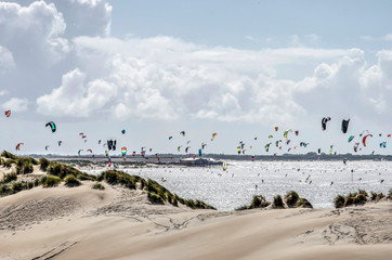 Coastline at Brouwersdam, Zeeland, the Nethrlands, with sandy dunes and hundereds of colorful kites under a cloudy sky
