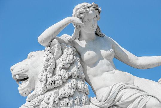 Ancient statue sensual renaissance era woman laying on big lion in Potsdam, Germany