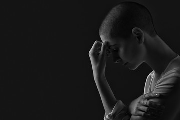 Sad, frightened and depressed female cancer patient portrait on dark background with copy space. Breast cancer patient, head in hands, black and white portrait.